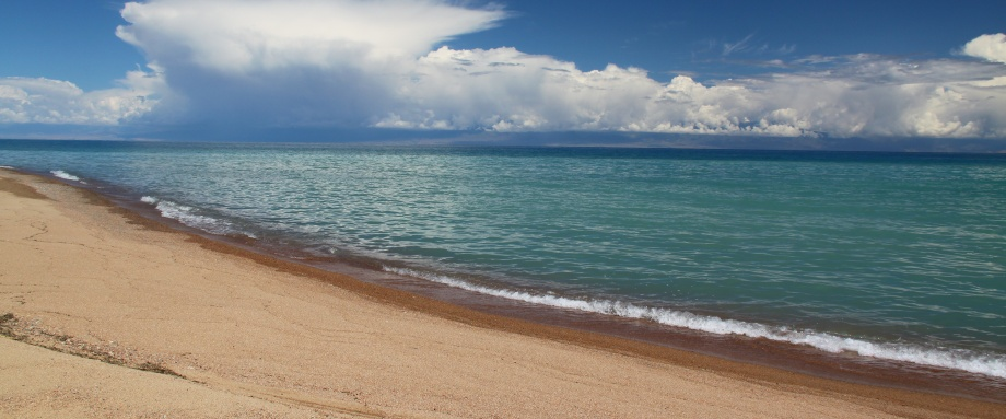 Snowy mountains and golden sands of Issyk Kul Lake